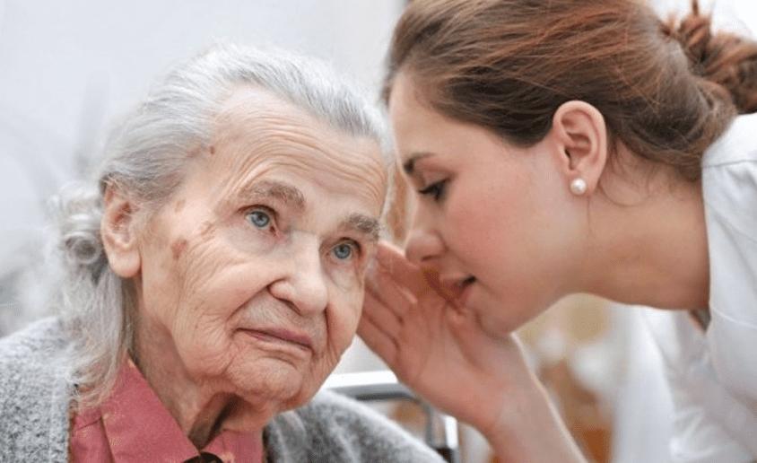 Mujer mayor con demencia y un cuidador comunicándose con el paciente